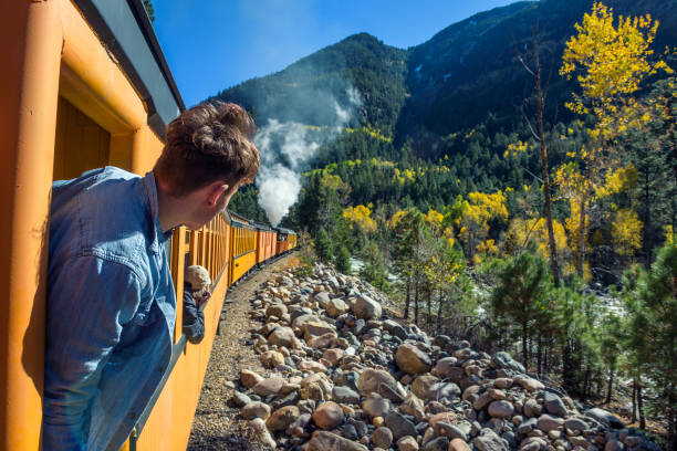Young man looking out of train window Young man looking out of train window on the historic steam engine train travelling from Durango to Silverton along the Animas River in Colorado, USA. rocky mountains north america stock pictures, royalty-free photos & images