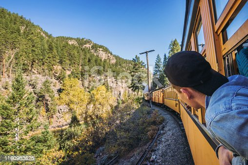 Young man with a cap looks out of train window on the historic steam engine train travelling from Durango to Silverton along the Animas River in Colorado, USA.