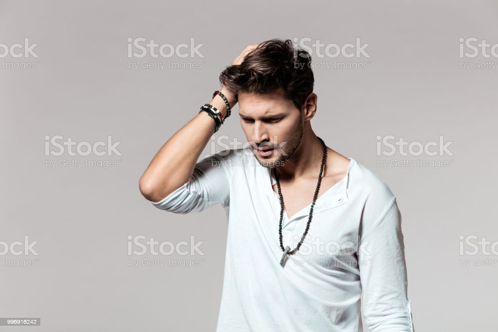Young man looking stressed on grey background Portrait of young man standing with hands on head over grey background 25-29 Years Stock Photo