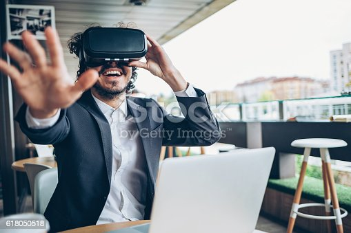 istock Young man looking through a virtual reality and gesturing 618050518