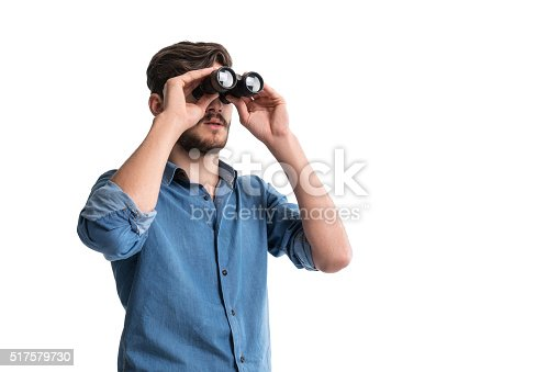 Young man looking through binoculars on isolated white background. Image taken with Sony A7RII camera system and developed from camera RAW.