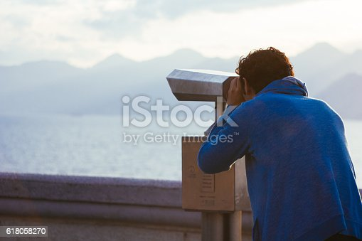 Young man looking through coin operated binocular to mountains and sea.