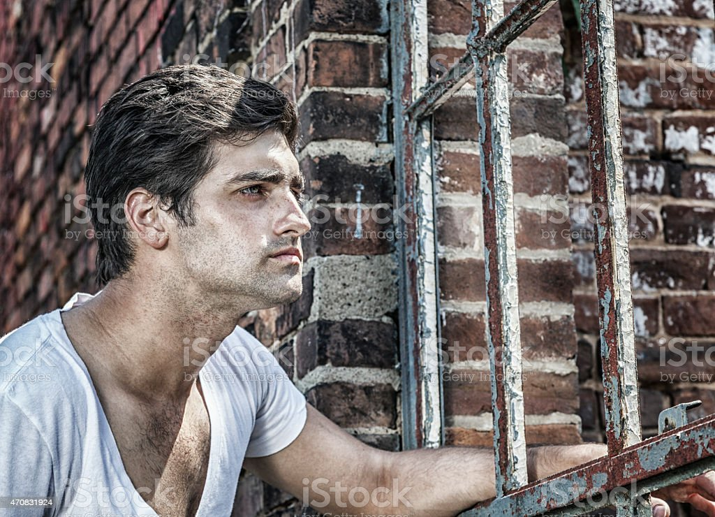 Young Man Looking Through Rusty Antique Window Frame stock photo