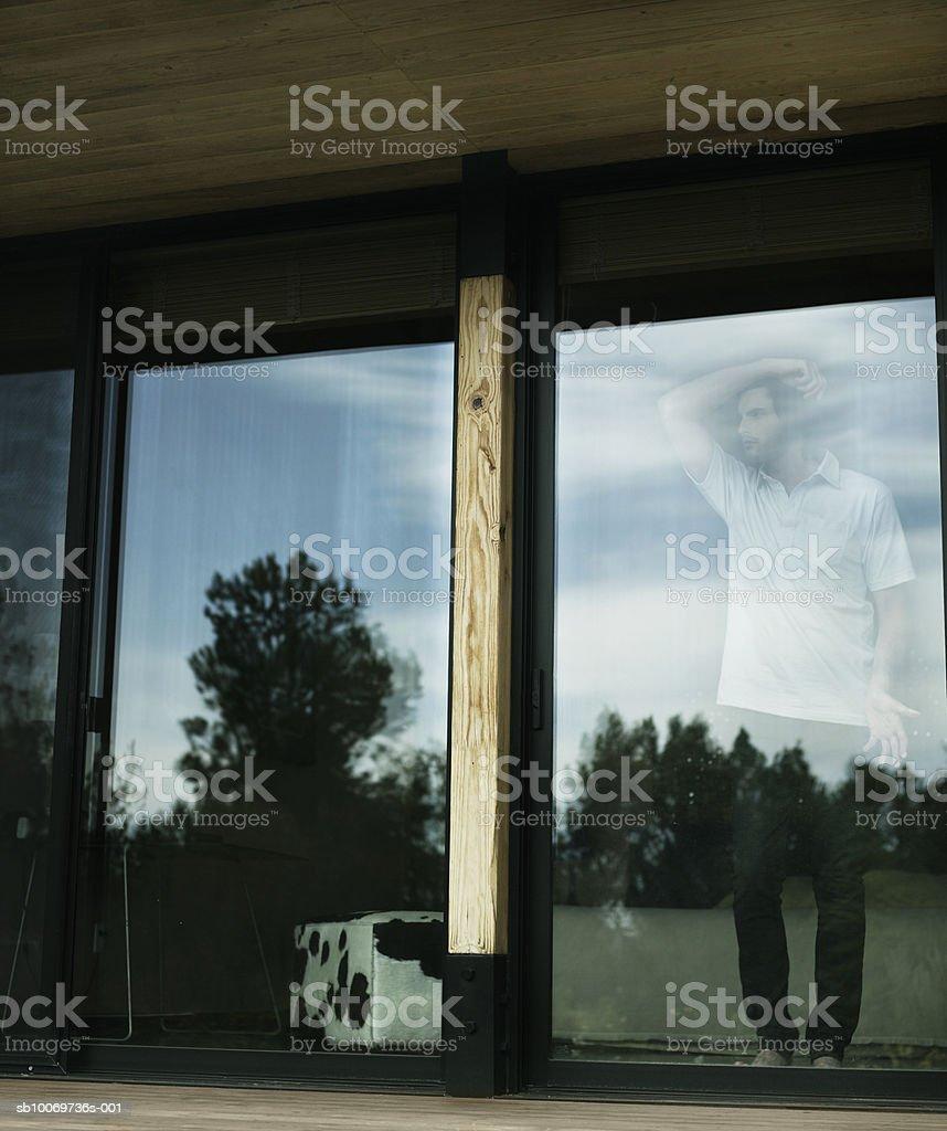 Jeune homme regardant par la fenêtre photo libre de droits