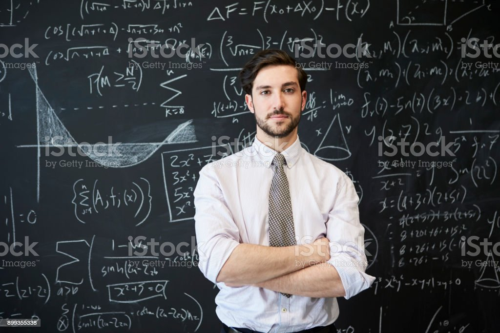Young man looking to camera in front of a blackboard stock photo