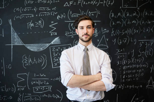 young man looking to camera in front of a blackboard - professore foto e immagini stock