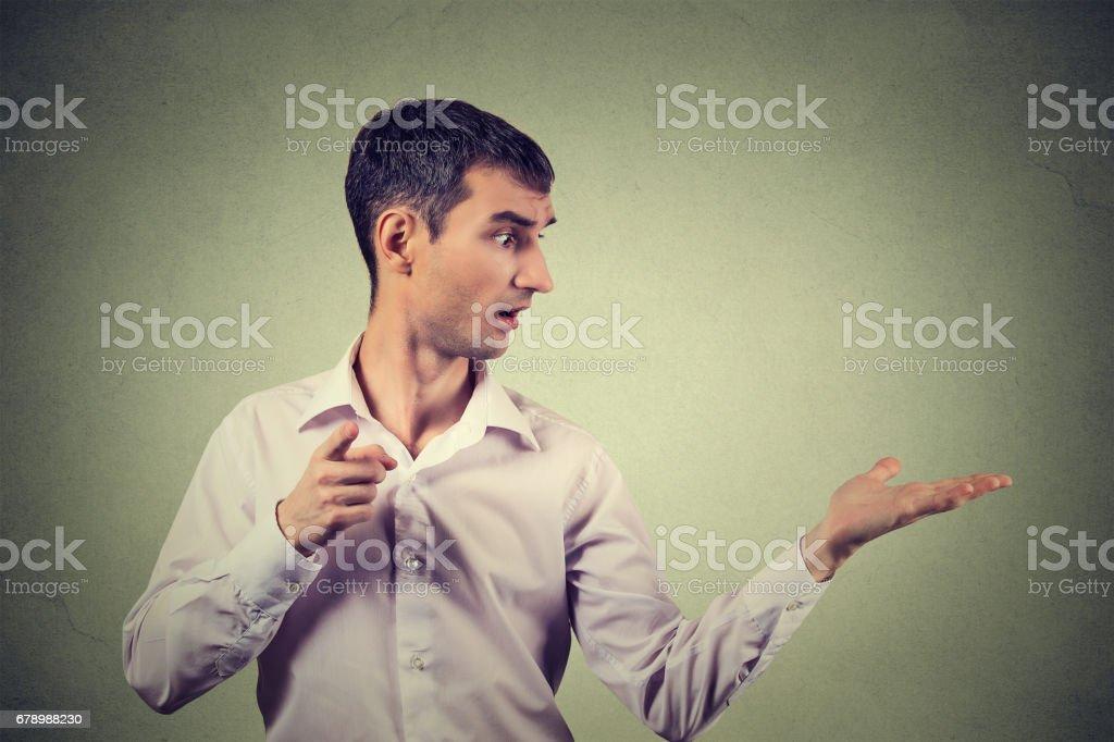 genç adam bir şey ya da birisi tarafından sürpriz kamera işaret ederken tarafına bakan royalty-free stock photo
