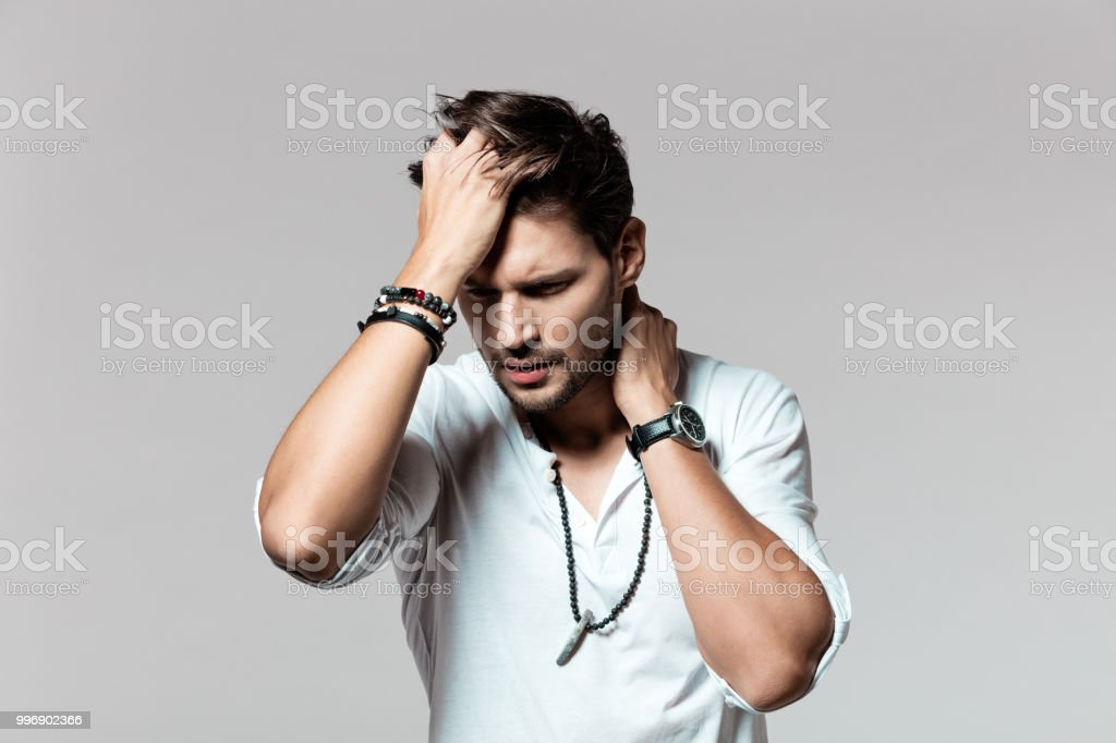 Young man looking totally stressed out Portrait of young man looking totally stressed out on grey background 25-29 Years Stock Photo