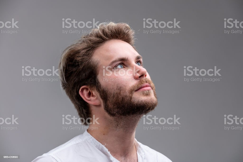 Young man looking up while thinking of a new idea royalty-free stock photo