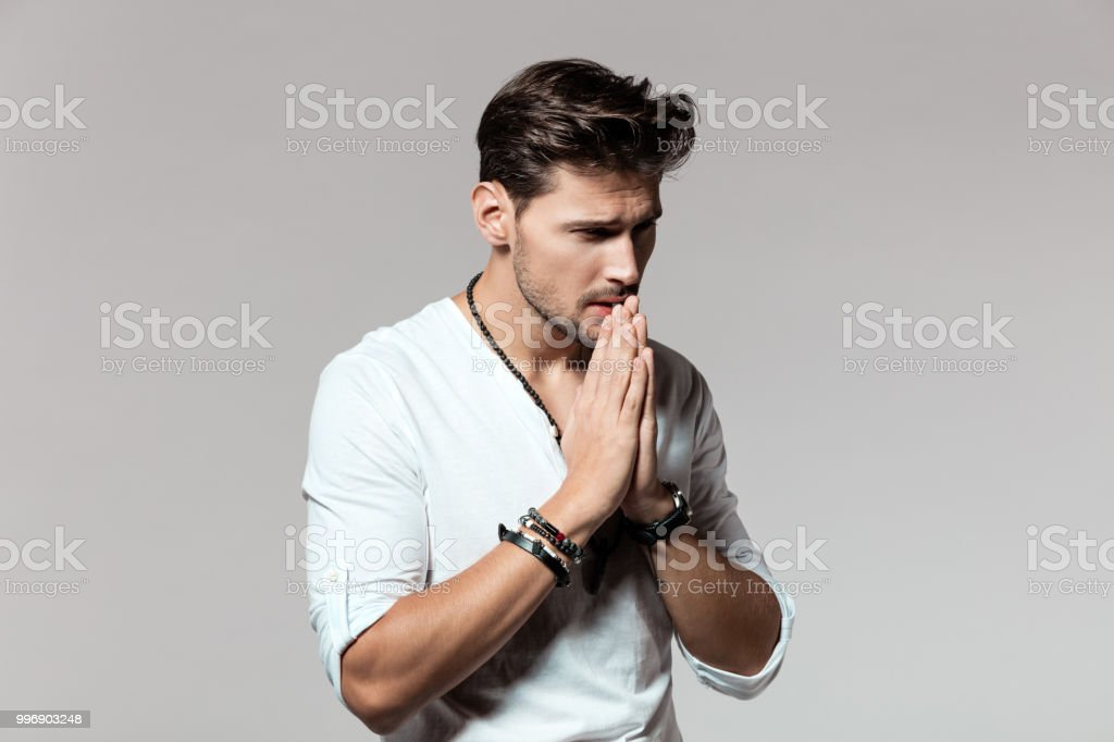 Young man looking worried Portrait of young man joining his hands with worried expression over grey background 25-29 Years Stock Photo