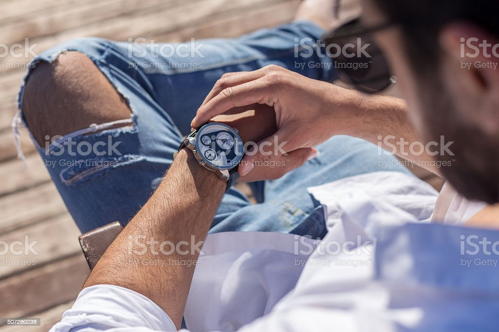 Young man looking wristwatch stock photo