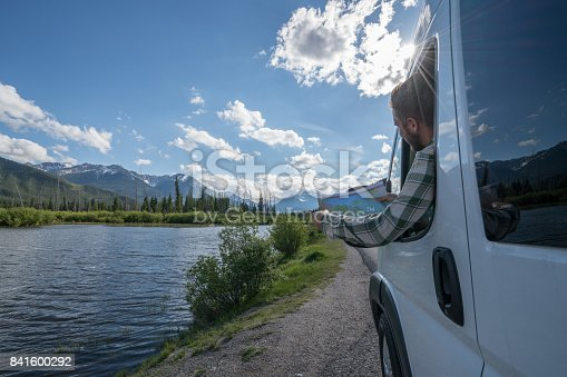 841604240 istock photo Young man looks at road map near mountain lake 841600292