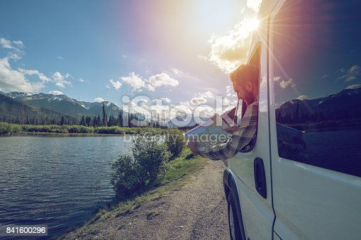 841604240 istock photo Young man looks at road map near mountain lake 841600296