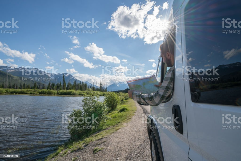 Young man looks at road map near mountain lake stock photo