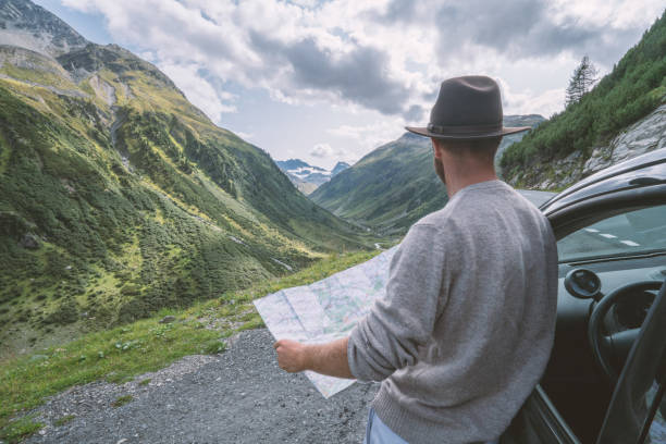 young man looks at road map near on mountain road, switzerland - road map stock photos and pictures