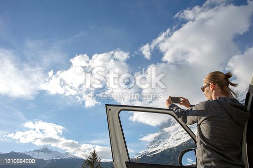 527894422 istock photo Young man looks off to mountains from car door 1210664200
