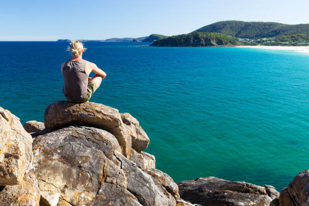 Young Man Looks Over Coastal View from a High Vantage Point stock photo