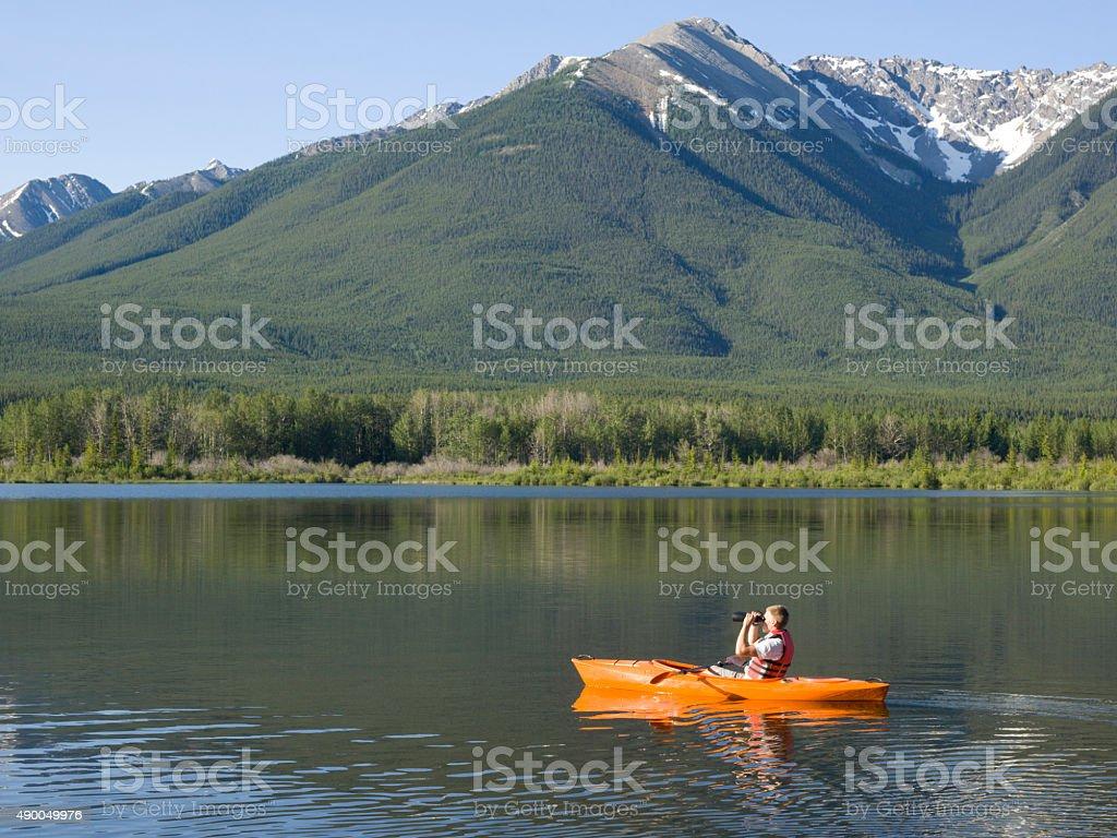 Young man looks through binoculars while kayaking stock photo