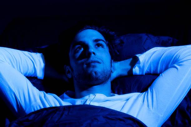 Young man lying awake foto