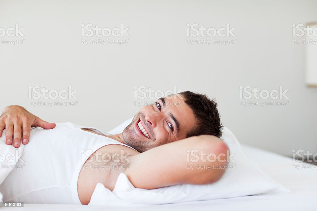 Young man lying down in bed and smiling royalty-free stock photo