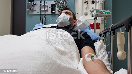 1049772134istockphoto Young man lying in hospital bed. Recovering in modern hospital wards, covered with blanket, face mask and with intravenous needle in his arm 1173091386