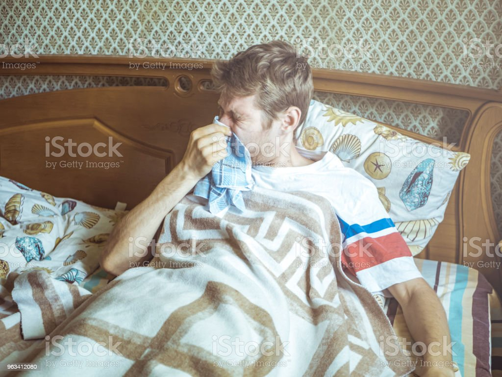 young man lying in the bed sneezing and blowing nose with handkerchief - Zbiór zdjęć royalty-free (Alergia)