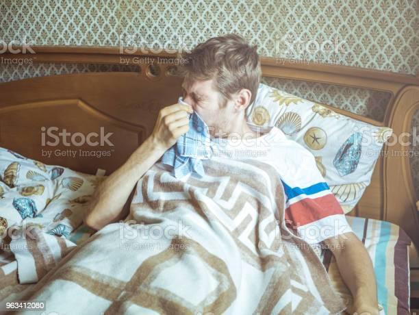 Młody Człowiek Leżący W Łóżku Kichający I Dmuchanie Nos Z Chusteczką - zdjęcia stockowe i więcej obrazów Alergia