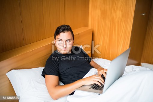 istock Young man lying in the bed working on a laptop at home 841365570