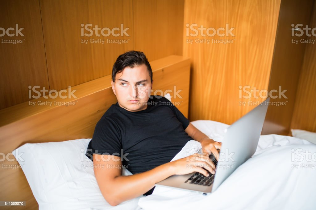 Young man lying in the bed working on a laptop at home stock photo