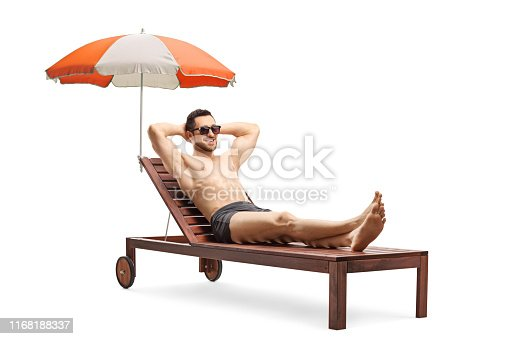Full length shot of a young man lying on a sunbed under umbrella isolated on white background