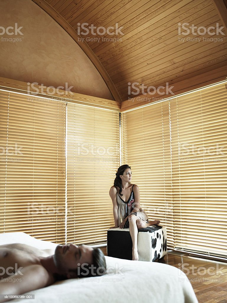 Young man lying on bed, young woman sitting on cube 免版稅 stock photo
