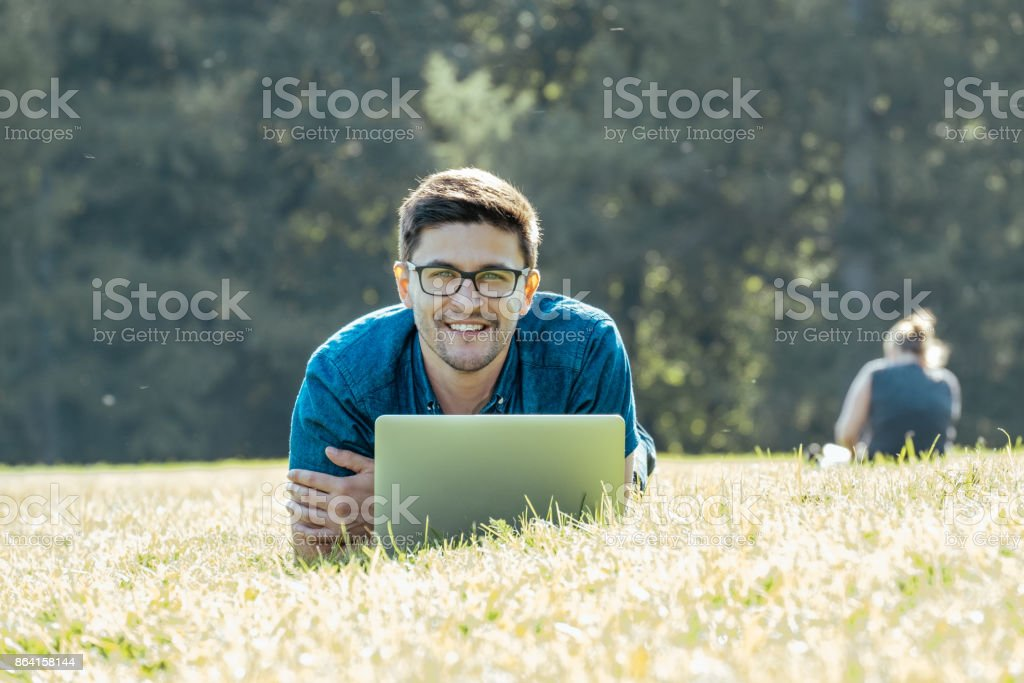 Young man lying on grass and using his laptop computer royalty-free stock photo