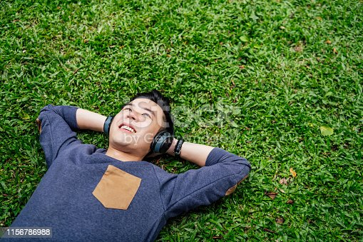Happy young Chinese man enjoying music, lying with hands behind head on grass, happiness, contemplation, escapism