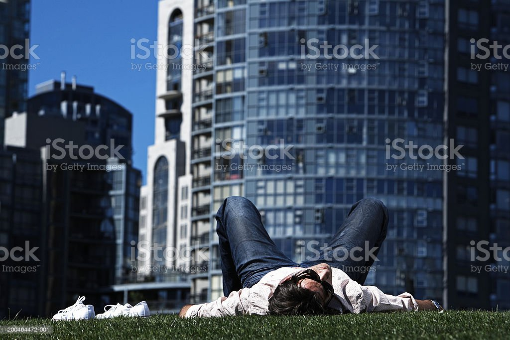 Young man lying on grass, wearing sunglasses, ground view royalty-free stock photo