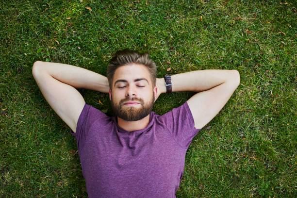 Young man lying on ground in park outdoors with eyes closed stock photo
