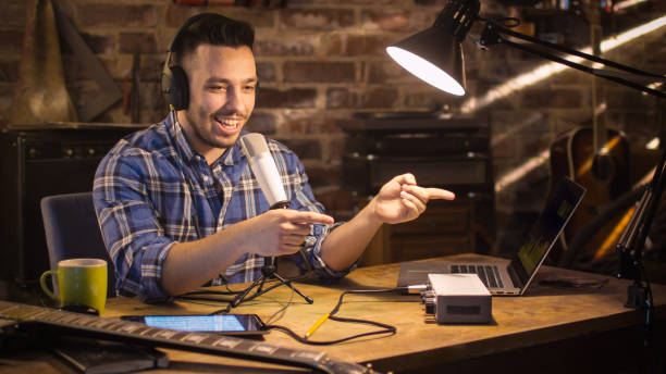 Young man makes a podcast audio recording at home in a garage. Young man makes a podcast audio recording at home in a garage. radio dj stock pictures, royalty-free photos & images