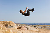 istock Young man makes extreme jump-overturn over stones. 120877605