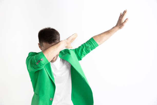 Young man makes the dab movement with his arms on a gray background. stock photo