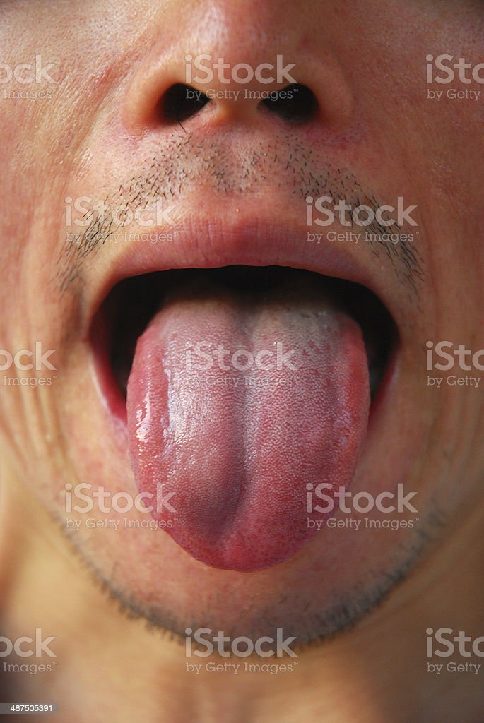 Young man making a face with his tongue stock photo