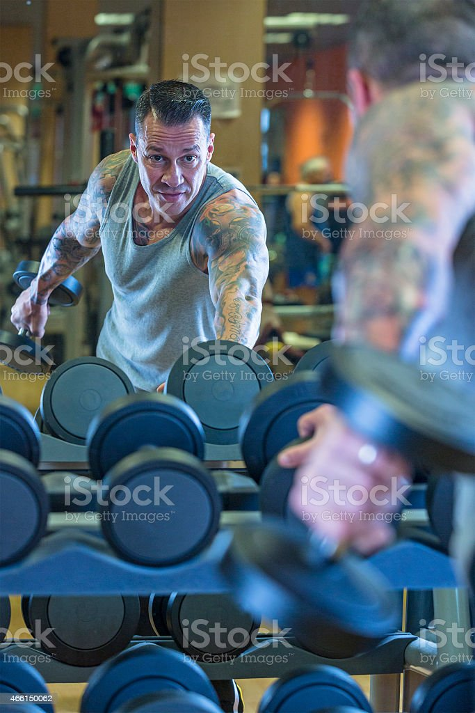young man making dumbbell kickback - workout routine stock photo