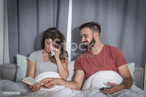 Young man making fun and laughing because his girlfriend crying while she reading a book in the bed and cry