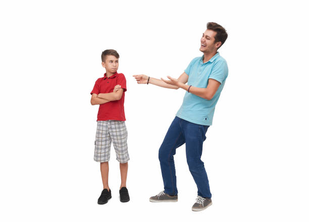 Young man making fun of little boy over a white background stock photo