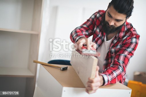 452592895 istock photo Young man making his own furniture at home 934701726