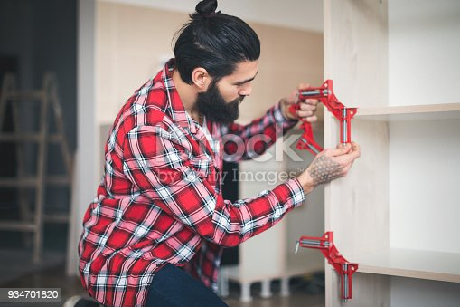 452592895 istock photo Young man making his own furniture at home 934701820