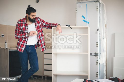 452592895 istock photo Young man making his own furniture at home 934702206