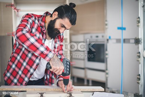 452592895 istock photo Young man making his own furniture at home 934706388