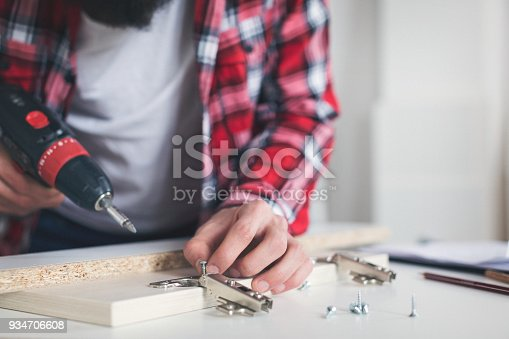 452592895 istock photo Young man making his own furniture at home 934706608