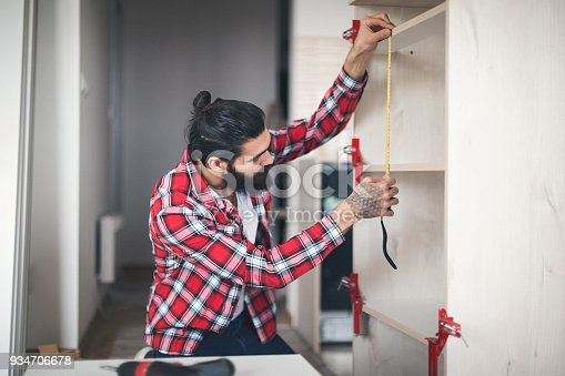 452592895 istock photo Young man making his own furniture at home 934706678