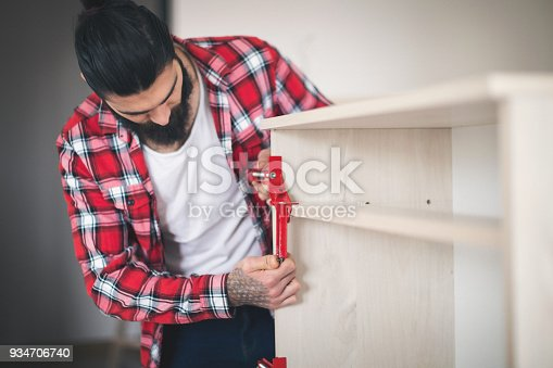 452592895 istock photo Young man making his own furniture at home 934706740