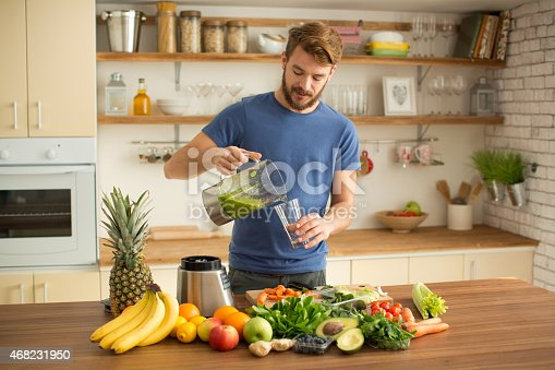 istock Young man making juice or smoothie in kitchen. 468231950